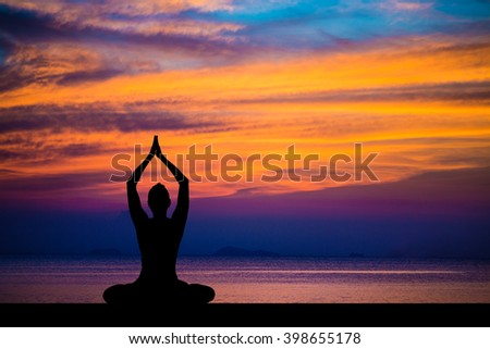 Silhouette of woman on the background of the stunning sea and sunset making yoga exercises, relax, peace.