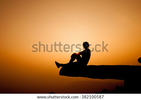 silhouette of woman on top mountain at sunset, evening light, selective focus