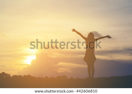 Silhouette of woman open arms under the sunrise