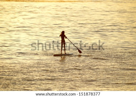 silhouette of woman paddleboarding at sunset, malibu, california, recreation sport paddling ocean beach surf