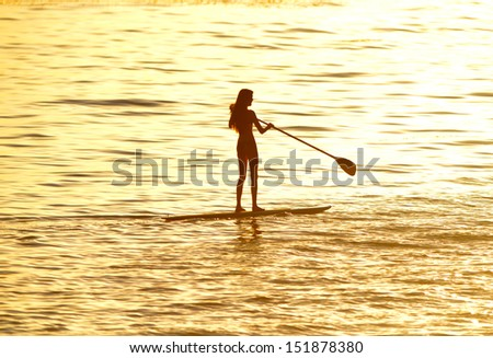 silhouette of woman paddleboarding at sunset, malibu, california, recreation sport paddling ocean beach surf orange sunlight reflection hue on water - stock photo