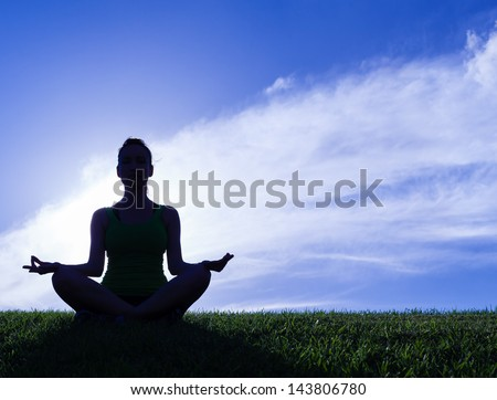Silhouette of woman practicing yoga - stock photo