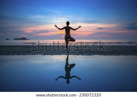 Silhouette of woman practicing yoga during sunset at seaside. - stock photo