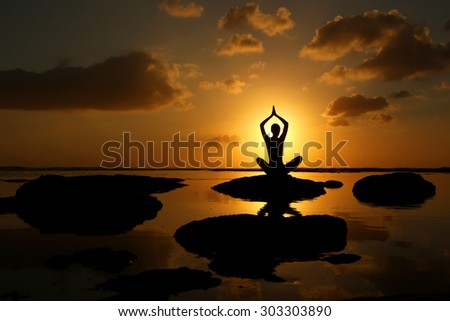 Silhouette of woman practicing yoga during sunset at the seaside  - stock photo