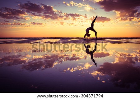 silhouette of woman practicing yoga on the beach at sunset - stock photo