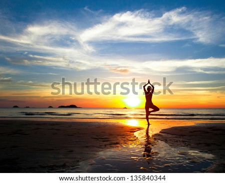 Silhouette of woman practicing yoga on the beach during a beautiful sunset - stock photo
