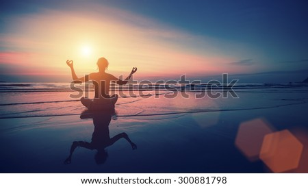 Silhouette of woman practicing yoga with the reflection on the wet sand during surrealistic sunset at the seaside.  - stock photo