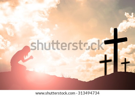 Silhouette of woman praying with cross over beautiful sky background
