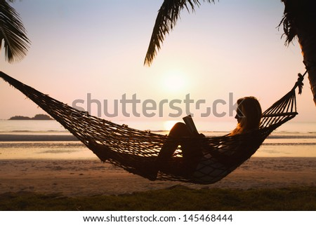 silhouette of woman relaxing in hammock on the beach - stock photo