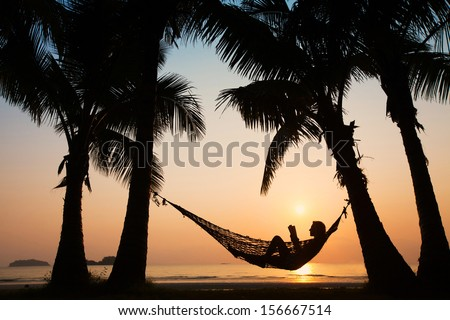 silhouette of woman relaxing in hammock with the book - stock photo