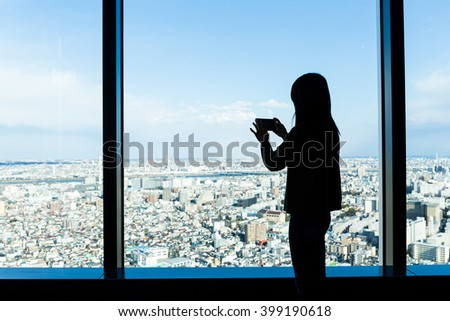 Silhouette of woman shooting photo on Tokyo city - stock photo