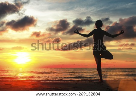 Silhouette of woman standing at yoga pose on beach during amazing sunset. - stock photo
