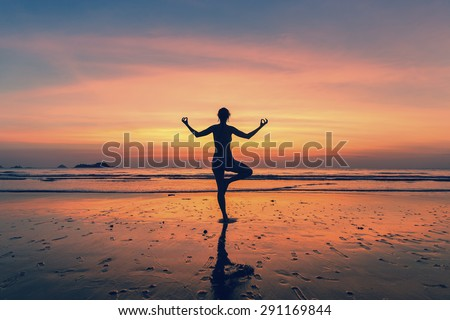 Silhouette of woman standing at yoga pose on the beach during fantastic sunset.