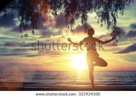 Silhouette of woman standing at yoga pose on the beach during sunset. - stock photo