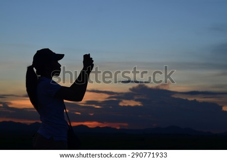 Silhouette of woman take a  photo  at sunset