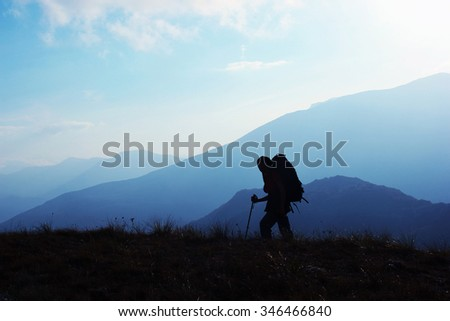 Silhouette of woman trekker with backpack in the mountains