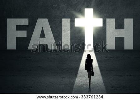 Silhouette of woman walking toward faith door - stock photo