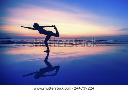Silhouette of woman with reflection, doing exercises on the beach during sunset.
