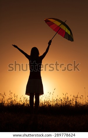Silhouette of woman with umbrella at sunset