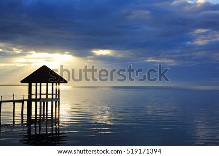 Silhouette of wood landing and sunbeam through heavy sky, dramatic clouds at sunrise with pavilion in the sea at Black Sand Beach, Trat