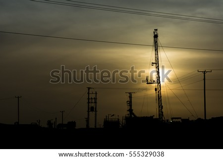 Silhouette of work over rig mast in the oil field