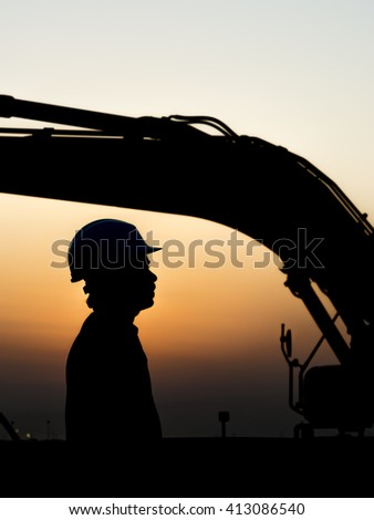 Silhouette of  worker at construction site - excavator loader in the background - oilfield  - stock photo