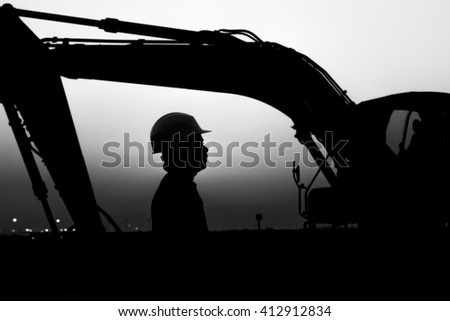 Silhouette of worker at construction site in oilfield. heavy equipment background - sunset -black and white  - stock photo