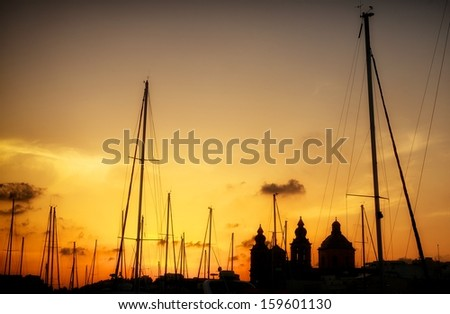 Silhouette of yachts poles and church on sunset hours, fragment photo of yacht pier on sunset, cropped, artistic photo, yachts and buildings silhouettes in sunset light, night scene - stock photo