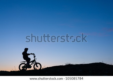 Silhouette of 4 years old boy on bike against sunset - stock photo