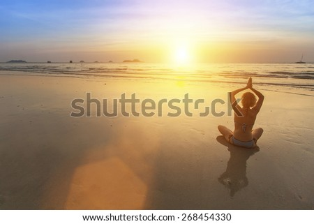 Silhouette of Yoga woman doing meditation near the ocean beach.  - stock photo