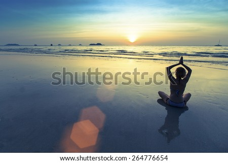 Silhouette of yoga woman meditating on the ocean beach.  - stock photo