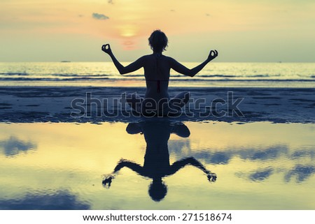 Silhouette of yoga woman meditating on the ocean beach. Fitness and Yoga. - stock photo