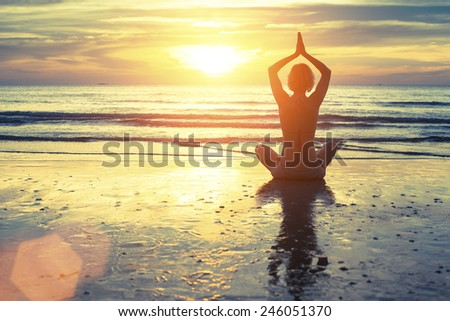 Silhouette of yoga woman meditating on the ocean beach. Fitness. Healthy lifestyle. - stock photo