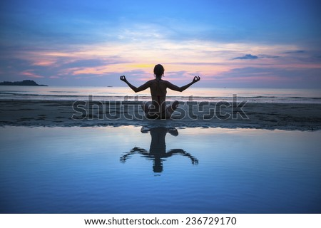 Silhouette of yoga woman meditating on the ocean beach. Yoga and fitness. - stock photo