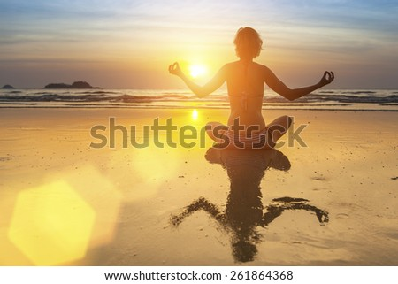 Silhouette of yoga woman on sea sunset.