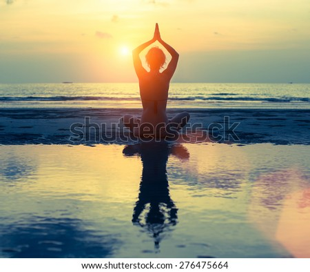 Silhouette of yoga woman on sea sunset in bright colors, reflection in the water. - stock photo