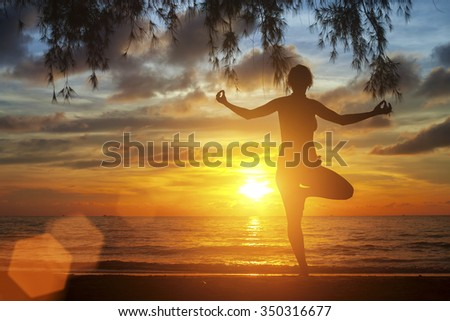 Silhouette of yoga woman standing on the beach during an sunset.