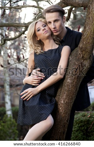 Silhouette of young adult couple in love posing in classic elegance dress to date - stock photo
