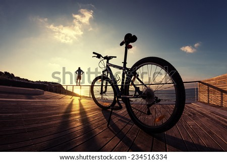 silhouette of young and active sportsman and his mountain bike standing on the railing near the ocean and looking far away at the sunset  - stock photo