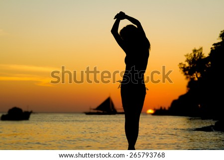 silhouette of young beautiful woman on tropical sunset sea background - stock photo
