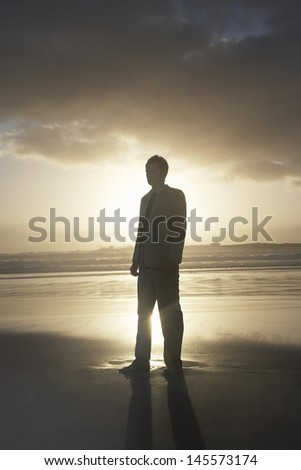 Silhouette of young businessman standing on beach at sunset