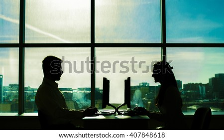 Silhouette of Young couple businessman on table solve theirs problem. business man show new options capability on pc computer women sit at board in office room space. type print text loot at screen - stock photo