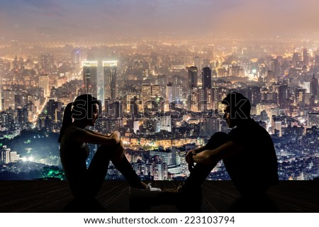 Silhouette of young couple face to face sit on ground in the city night. - stock photo