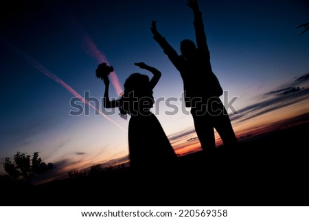 Silhouette of Young couple in love bride and groom posing in a field on beautiful sky sunset background, in their wedding day in the summer,jumping. Series. - stock photo