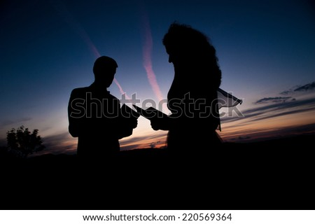 Silhouette of young couple in love bride and groom posing in a field on beautiful sky sunset background, in their wedding day in the summer and reading a book. Series. - stock photo