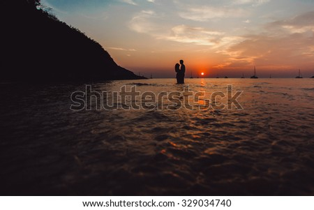 Silhouette of young couple in love posing at sunset on the beach sunset,cool amazing view,honeymoon on paradise island,maldives,bali,bahamas,hawaii.Kissing couple on beach sunset