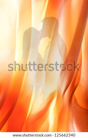 Silhouette of young couple kissing behind curtain. - stock photo