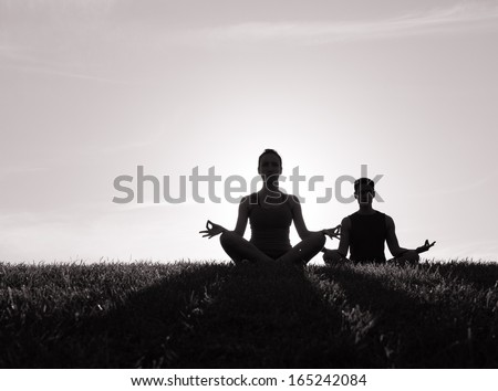 Silhouette of young couple meditating  - stock photo