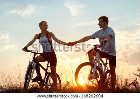 Silhouette of young couple on sporty bicycles against sunset - stock photo