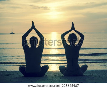 Silhouette of young couple practicing yoga on sea beach during sunset. Cross-process photo style.